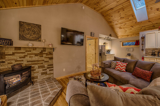 Living area with TV and fireplace in Mountain Creek Cabin in Maggie Valley, NC